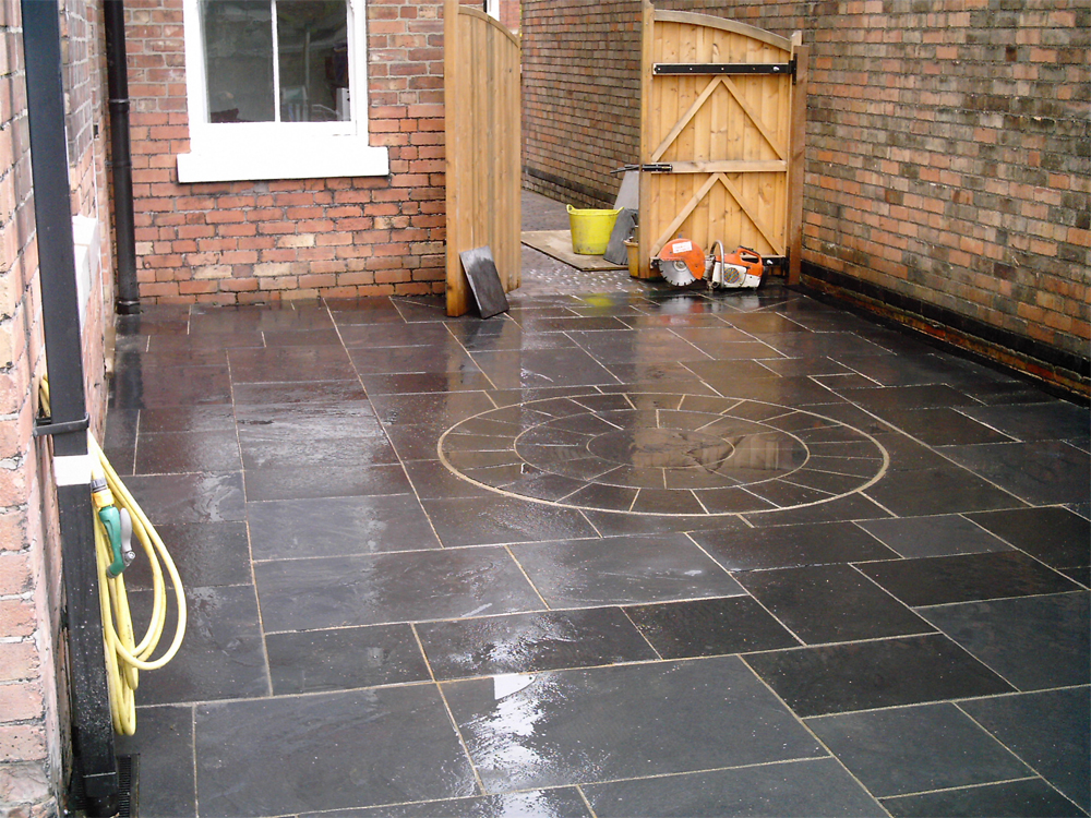 Black Limestone Circle and Paving (pictured here when wet). Private garden built by PJ Landscapes.