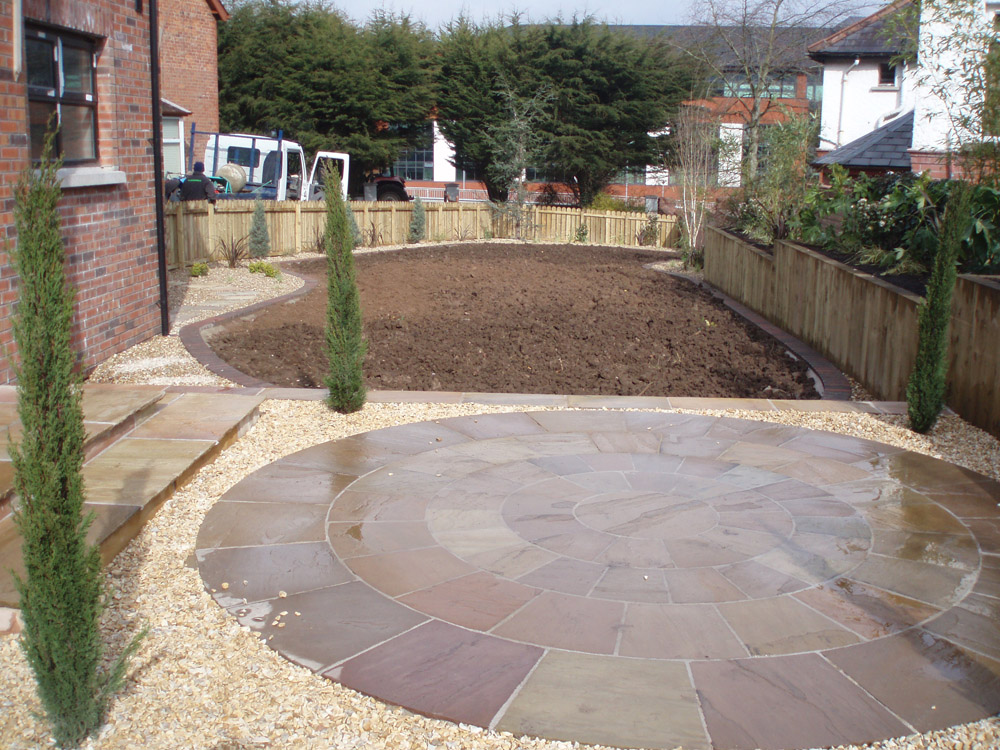 Beige Riven Sandstone Circle & Paving (pictured here when wet) with Buff Flint Gravel. Private garden' Ireland' by Maurice Maxwell Garden Designs.