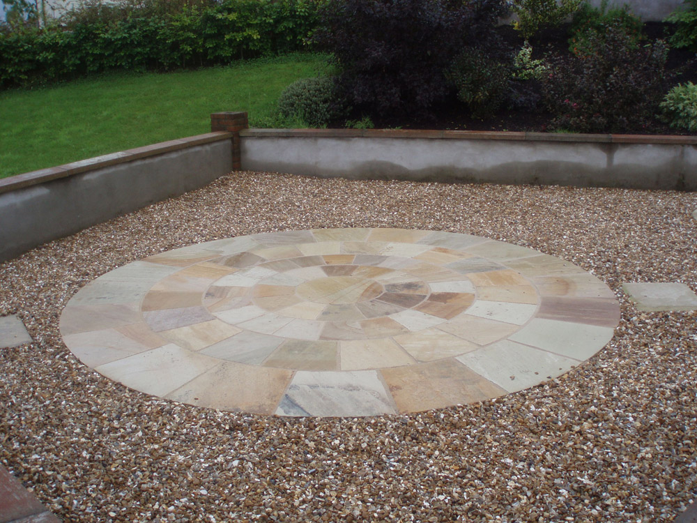Golden flint gravel 20mm with a green riven sandstone circle. Private garden in Ireland designed and built by Maurice Maxwell Garden Designs.