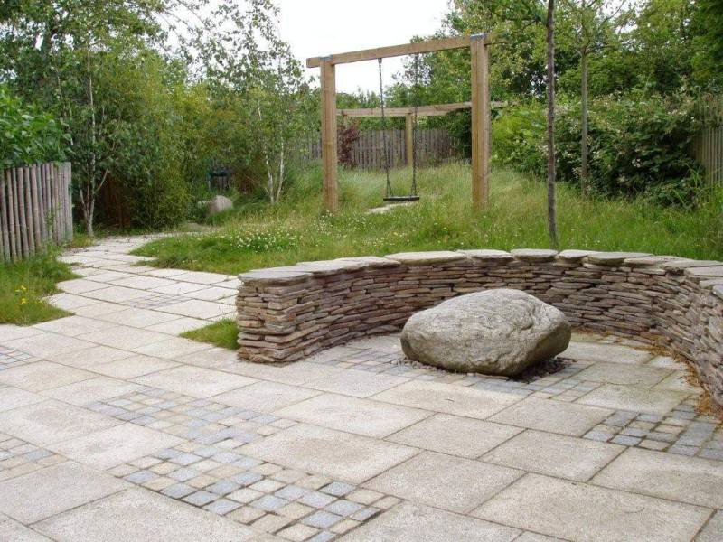 Yellow Granite Paving with Yellow & Blue/Grey Sawn Setts' Yellow Paddlestone Walling and a mixed glacial boulder in a Private Garden. Designer - Julie Toll Ltd. Contractor - Brambles Garden Services.
