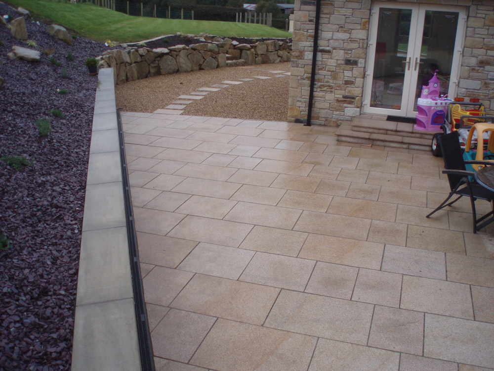 Yellow granite paving (pictured here when wet) with plum slate shale' golden flint gravel and buff sandstone rockery. Private garden' Ireland. For further images on this job please visit our projects gallery.