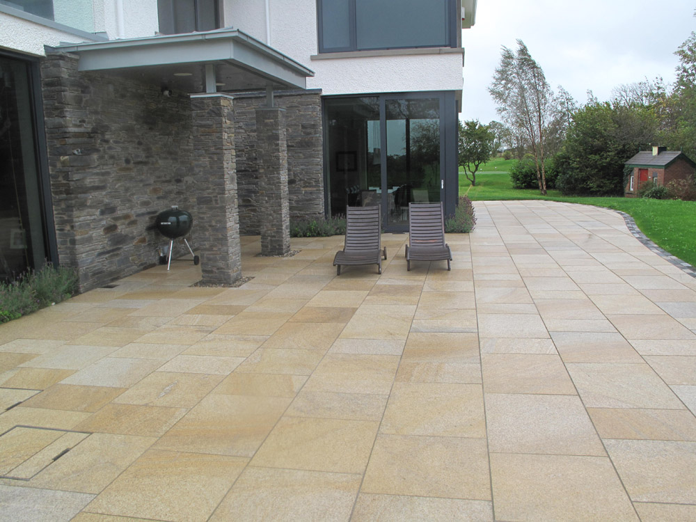 Yellow granite paving (pictured here when wet). Private garden in Ireland designed by Beth Moore and built by Ben McKee Landscapes. For further images of this job please visit our Projects Gallery.