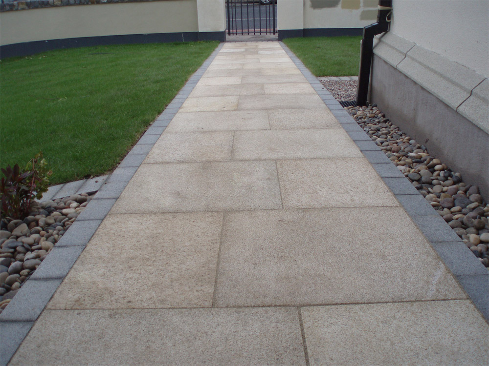 Yellow granite paving with blue grey granite setts and scottish beach pebbles. Private garden' in Ireland' designed by Maurice Maxwell Garden Designs and built by Spring Landscapes. For further images of this job please visit our Projects Gallery.