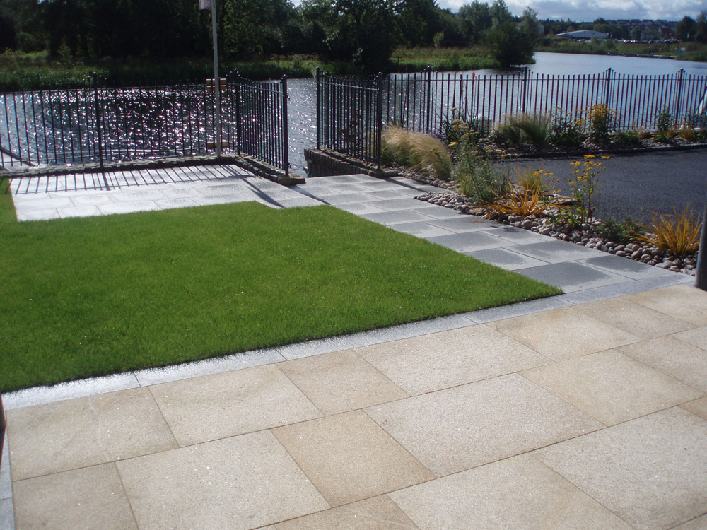 Yellow granite paving with silver grey granite kerb and blue grey granite paving. Private garden' in Ireland' designed by Maurice Maxwell Garden Designs and built by Spring Landscapes. For further images of this job please visit our Projects Gallery.