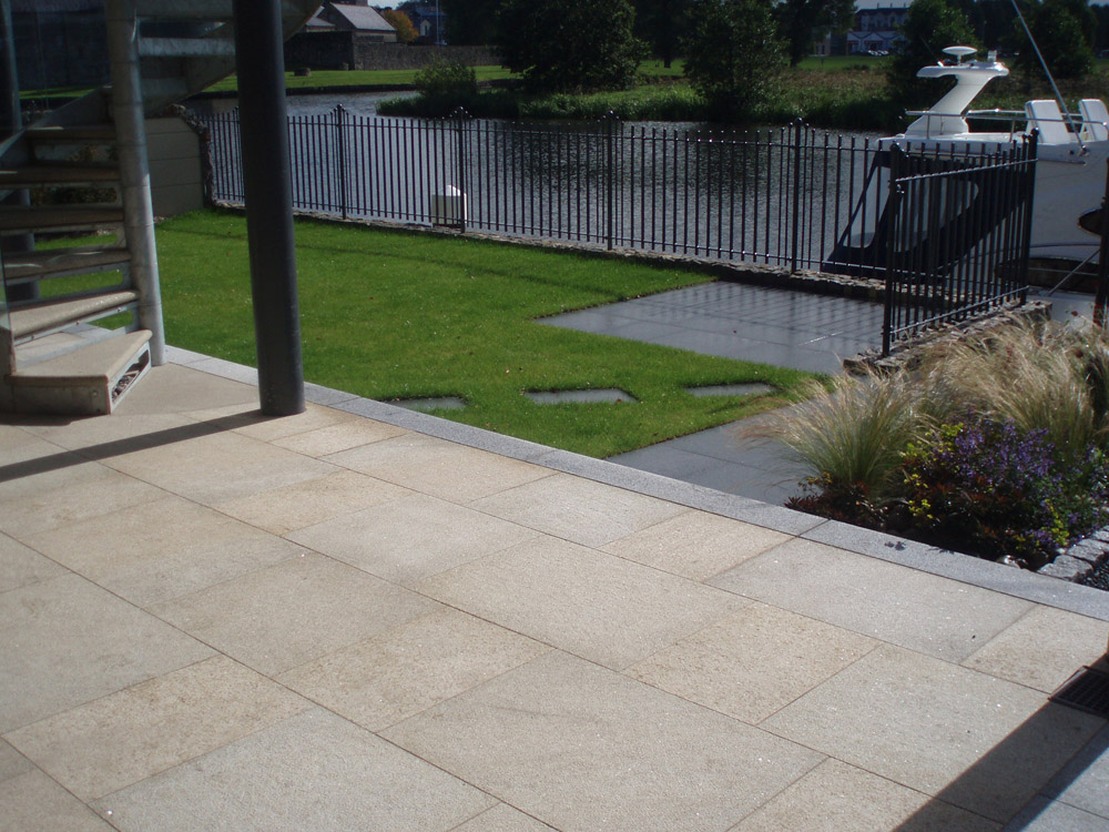 Yellow granite paving with silver grey kerb and wet blue grey granite paving. Private garden' in Ireland' designed by Maurice Maxwell Garden Designs and built by Spring Landscapes. For further images of this job please visit our Projects Gallery.