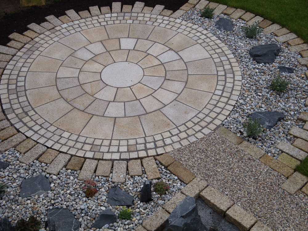 Yellow granite imperial setts with a yellow granite circle' yellow granite blocks 150x150xRL (these blocks are a bespoke product)' rounded flint stones and flint gravel laid in Cedagravel. Private garden designed and built by the home owner.