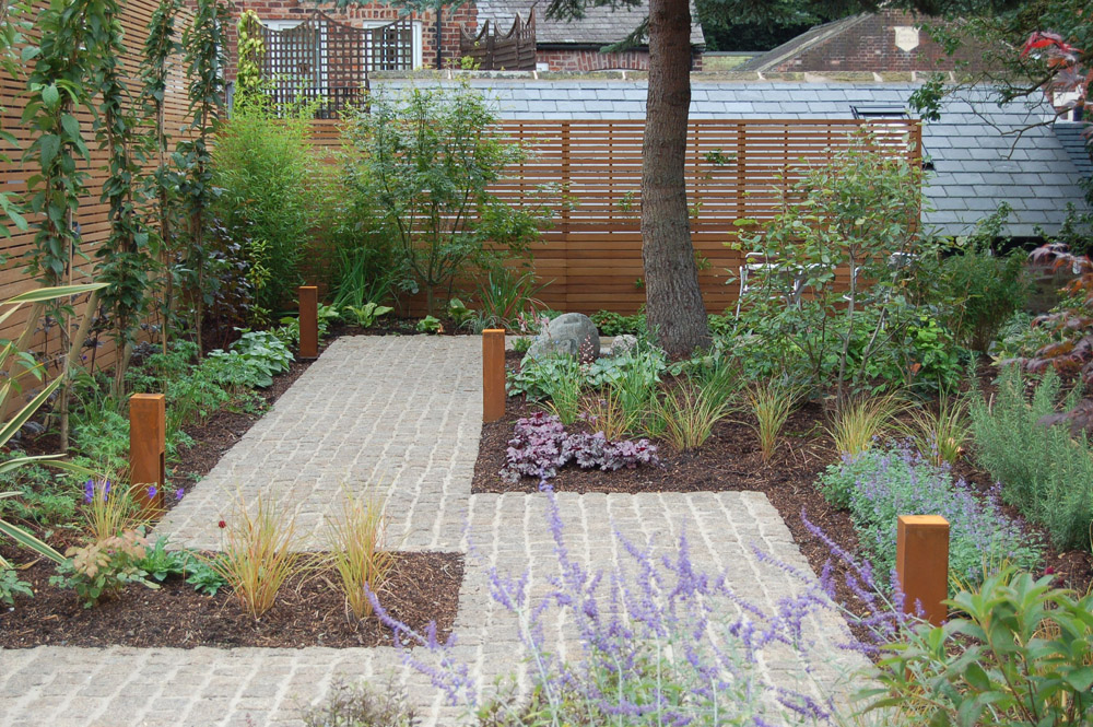 Yellow Granite Cropped Setts with Scottish Beach Cobbles and a Celtic Boulder. Private garden designed by Matt Nichol Garden Design and built by Creative Gardens & Driveways.