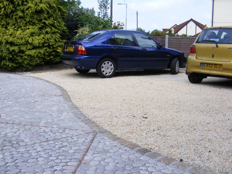 Cedagravel® filled with Barleycorn Quartz aggregate for a private driveway. Also used are the flat grey pebbles.